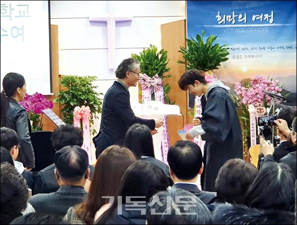 남북사랑학교 졸업식에서 심양섭 교장(왼쪽)이 졸업생에게 장학금을 전달하고 있다.