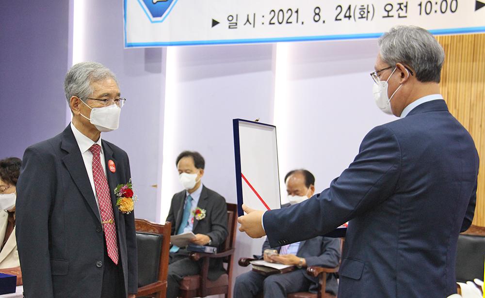 이임하는 정규남 총장에게 법인이사장 김용대 목사가 명예총장 추대패를 전달하고 있다.