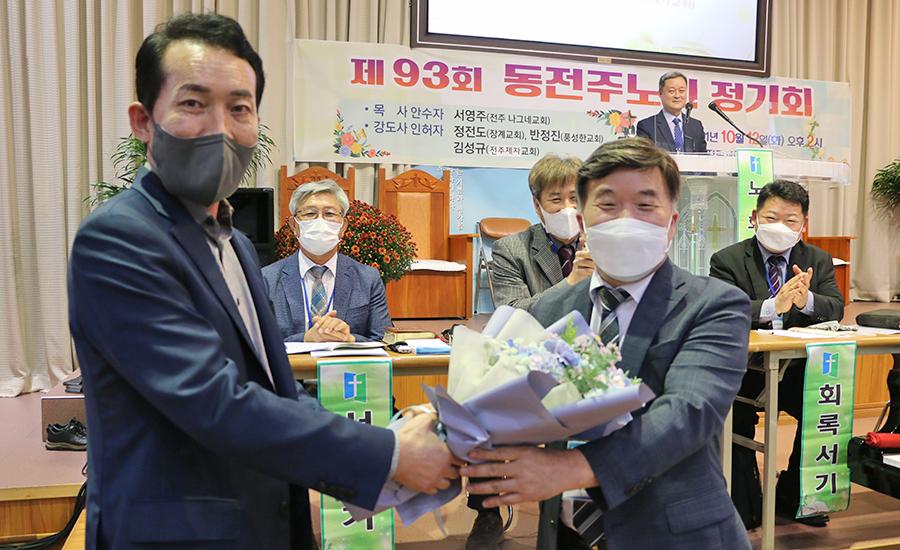 동전주노회 가을정기회에서 총회 부회록서기로 선출된 한기영 목사(사진 오른쪽)에게 축하 꽃다발이 전달되는 모습.